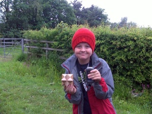 Isaac with the puzzle from the puzzle cache (in the rain!)