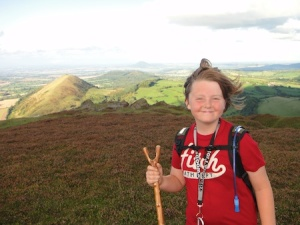 Isaac at the summit of Caer Caradoc with The Wrekin in the background